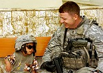 U.S. Army Sgt. 1st Class James Boucher smiles as an Iraqi child enjoys trying on his helmet and sunglasses