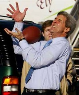 John Kerry tries to catch a football.