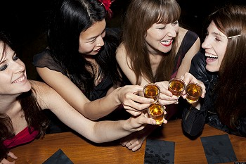 Women friends toasting with shots at a bar
